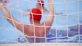 beach ball : Shot from behind the gates of male athletes playing water polo in outdoor pool in summer.