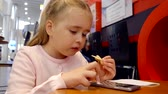 rágás : Close up portrait of a cute little girl eating in a cafe and playing games on smartphone.