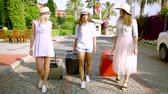 hostel : Three female friends in dresses and hats walking on the street with luggage.