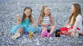 irmãs : Three happy children talking and playing on the pebble beach. Stock Footage