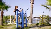 playground : Beautiful healthy woman working out on elliptical machine on sports ground.