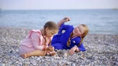 both : two little girls are sitting on pebble sea coast in daytime, calmly playing on a beach independently