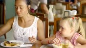 tea time : family of mother and daughter is eating during breakfast in morning in a restaurant, sitting at table