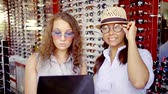 видя : young woman dressed funny, but stylish glasses and fooling around in the optics store