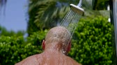 sunburn : portrait of a man who is standing under a shower in nature, o enjoying a cool stream