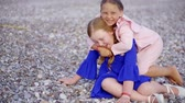 chilly : Two cute kids playing together on pebble beach in summer. Stock Footage