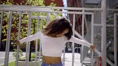 téma : young slim African American girl in white topic posing on camera holding hands behind the iron fence. a Sunny summer day