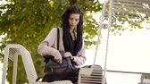 handbag : Young single woman with dreadlocks is sitting alone on a bench in a park. Stock Footage