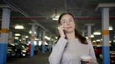 bussiness : Middle-aged woman is talking on the phone, drinking hot black coffee while walking in uderground garage. Stock Footage
