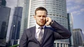 ответственность : Serious young handsome businessman is talking on a phone with a office and making deals.