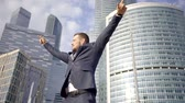миллионер : A young and happy man shows his emotions, he seems free and independent against the background of large business buildings