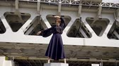 kabelka : stylish model girl in a dark blue long skirt is spreading her legs for a modern railway bridge. dance hand gestures Dostupné videozáznamy