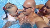 parentalidade : Close up shot of a happy family of three daughter mother and father spending time in a pool. Stock Footage