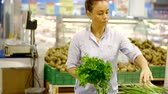grocer : Woman is holding a bunch of fresh green herbs in a supermarket. Stock Footage