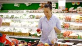 grocer : Female buyer chooses fresh red apples and puts them in a plastic bag in a grocery store.