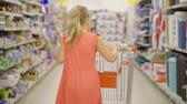 mercearia : girl of eight years carries a shopping cart along the shelves of a supermarket