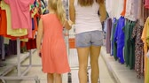 téma : girl of eight and her mother is carrying a shopping cart along the shelves of a supermarket section of clothes