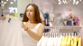 topic : Attractive woman chooses pullover in shopping Mall