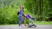 baby carriage : Parents take daughter for a walk in a stroller in summer. Mother and father take child outside in a park.