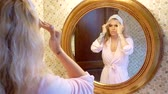 balzám : attractive blonde is standing in her bathroom and applies a moisturizer to the skin in front of a round mirror
