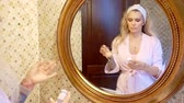 bálsamo : attractive blonde is standing in her bathroom and getting ready in the morning to apply a moisturizer to the face skin in front of a round mirror