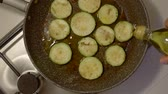 stir fried vegetables : Fried sliced zucchini in hot boiling oil. Close-up of the frying pan. hand pours extra olive oil from the bottle