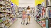 agd : slim brunette woman and her child daughter are walking in a supermarket between racks with goods Wideo