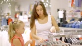 agd : mother and her child girl are watching on a hangers with clothing in a store, woman is taking items Wideo