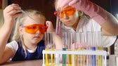 репетитор : preschooler pupil girl is counting drops and dripping in vials from a pipette in a chemical laboratory