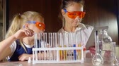 репетитор : child girl and adult woman is wearing chemical protective glasses are sitting at table with toy set for laboratory