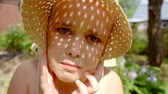 strohhut : funny little preschooler girl is playing with summer straw hat in a garden in sunny day, looking at camera
