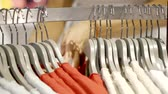 modern commerce : Close up shot of a plenty of different shirts hanging on the rack in boutique. Stock Footage