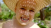 selfish : Close up portrait of a cute little girl making silly faces and having fun outside. Stock Footage