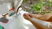 sanitário : Woman washing her hands in a washbasing outside in a garden.