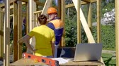 garanti : Builder in a protective helmet and vest. shows the woman to the customer deviations in the construction of the drawing of the house Stok Video