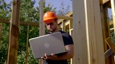 измерительный : Male builder with laptop on a construction site.
