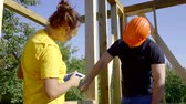 nível : Male and female workers building a house.