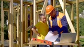 both : foreman and female worker of a construction of house are quarreling on a working area, man is waving papers Stock Footage