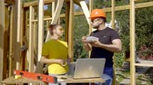 developing : male builder is eating lunch from box and chatting with his female colleague on a construction area in sunny day Stock Footage