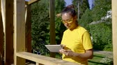 flatbed : designer woman is measuring detail of wooden house in a building area and writing data in a flatbed computer Stock Footage
