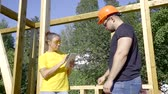 правитель : female designer and male foreman is examining building house in sunny day, he is measuring and she is filling data
