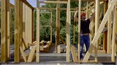 dimensões : adult man is making measurements of wooden beams in a frame of new house under construction, using tape and level