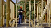 distances : builder is measuring distances in frame of wooden cottage in construction area in sunny summer day