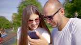 both : loving pair is resting in a park and watching photos in a smartphone, man is holding gadget