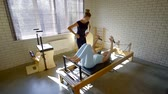 sportovkyně : Pilates teacher corrects the position of the clients body on the simulator. physical education of the body