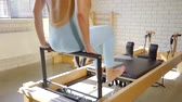 ayar : therapeutic exercise on the simulator Pilates. the girl exercises the feet Stok Video