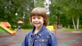 broadly : little dark haired child girl is running in a park over playground and smiling broadly, camera is moving