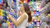 crocheting : adult woman is approaching to shelf with yarn in a shop for needlework and taking few of skein