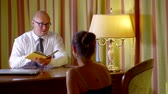 doradca finansowy : Businessman in glasses reading terms of a contract to a woman, reading from a diary.