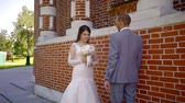 heteroszexuális párok : excited man is walking to his amazing pretty bride wearing white wedding dress, standing outdoors in sunny summer day Stock mozgókép